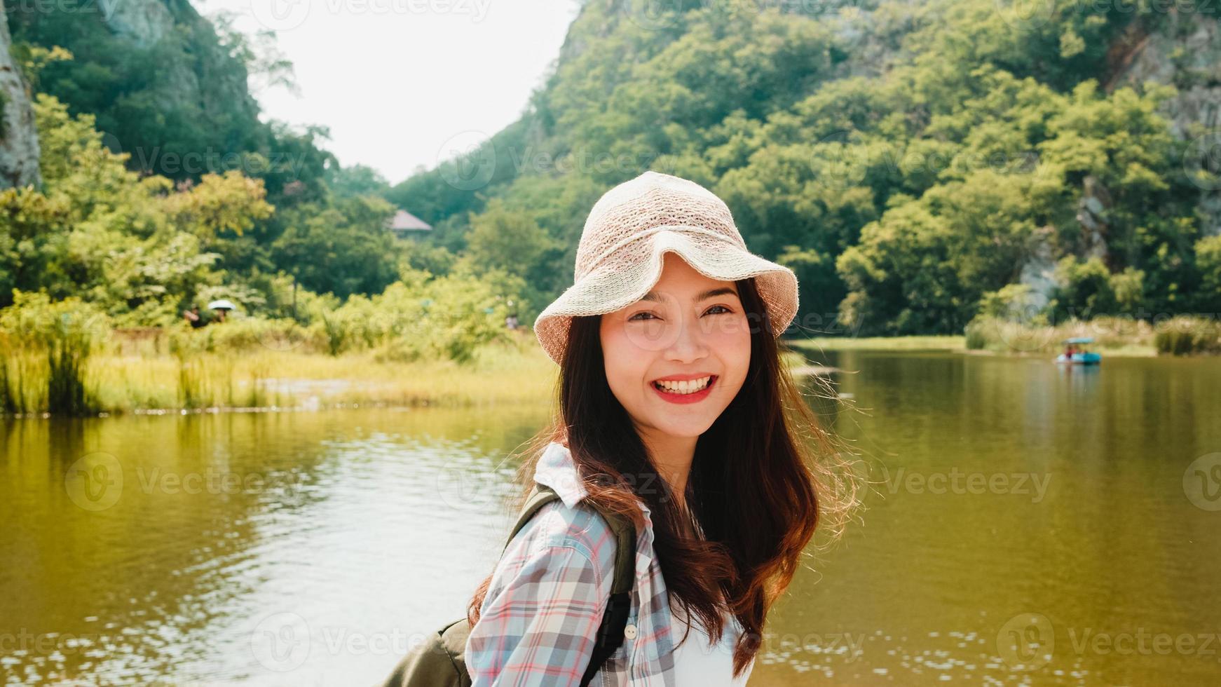alegre jovem viajante asiática com mochila caminhando no lago de montanha. adolescente coreana desfrutar de sua aventura de férias sentindo feliz liberdade. viajar de estilo de vida e relaxar no conceito de tempo livre. foto