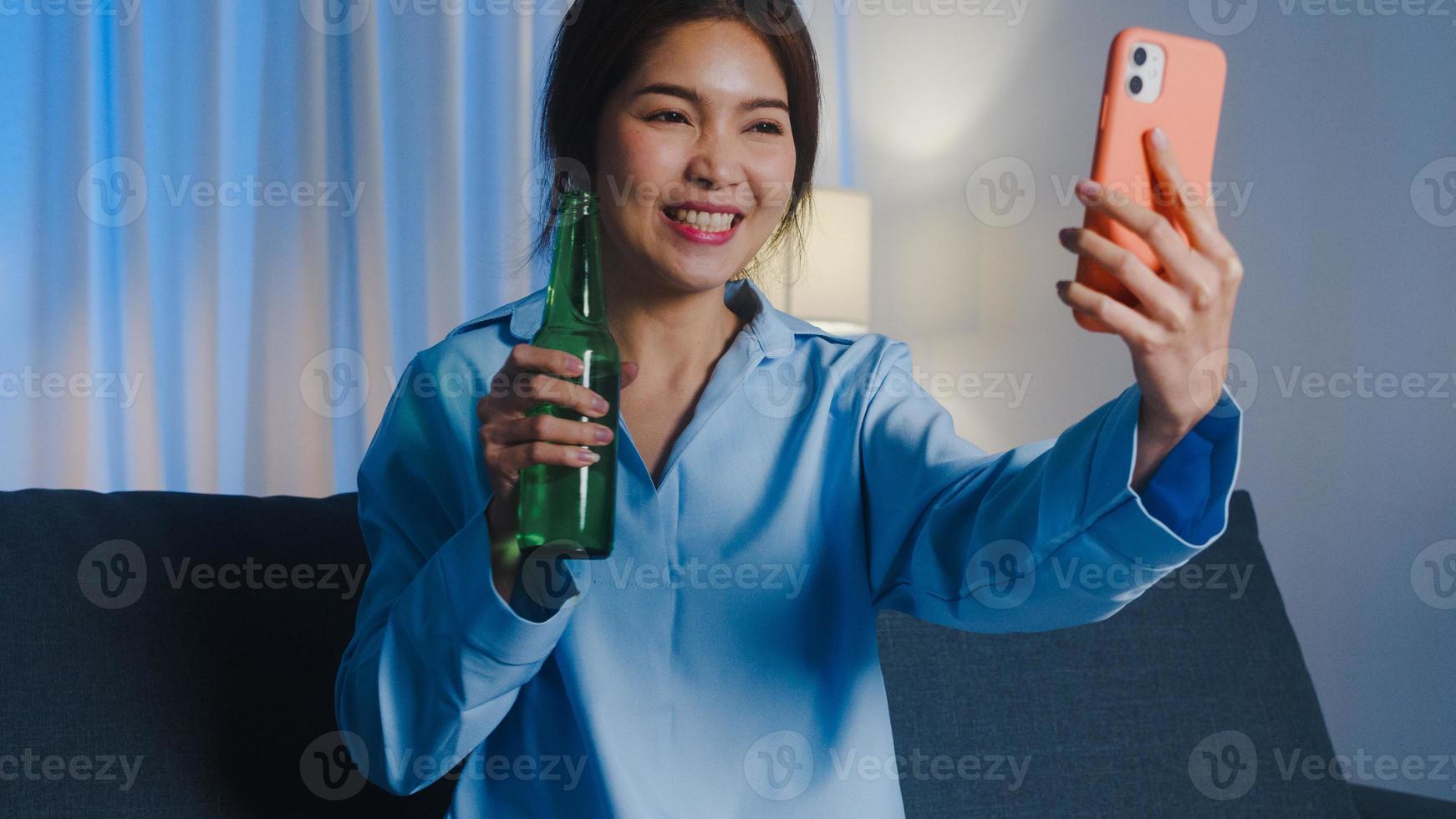 jovem senhora asiática bebendo cerveja se divertindo momento feliz noite festa evento on-line celebração através de chamada de vídeo na sala de estar em casa à noite. distanciamento social, quarentena para prevenção de coronavírus. foto