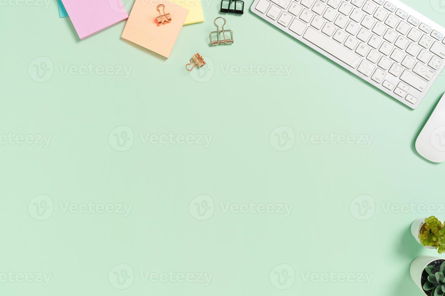 espaço de trabalho mínimo - foto criativa plana da mesa do espaço de trabalho. mesa de escritório de vista superior com teclado, mouse e livro sobre fundo de cor verde pastel. vista superior com espaço de cópia, fotografia plana leiga.