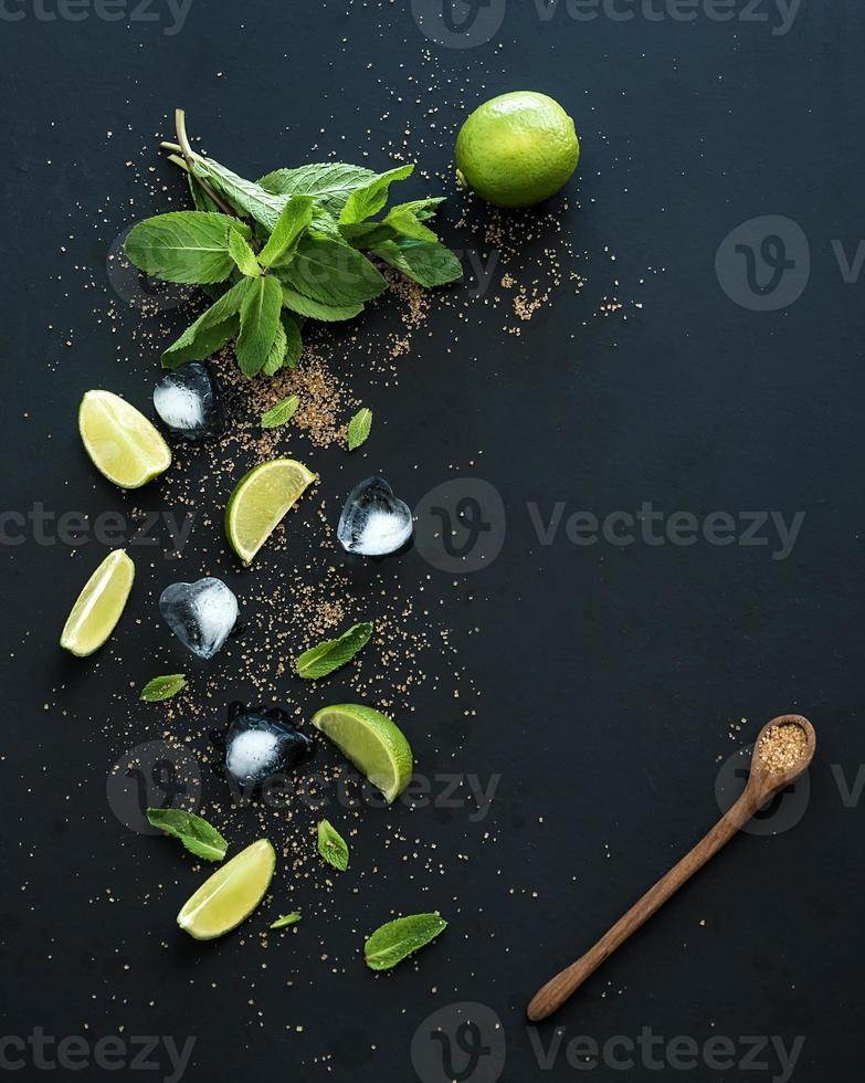ingredientes para o mojito. hortelã fresca, limão, gelo, açúcar sobre preto foto