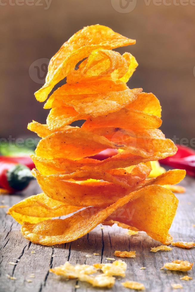Chips de páprica com pimenta em um fundo de madeira foto