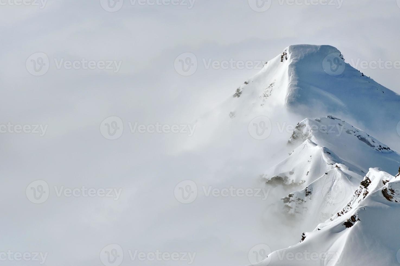 nevoeiro acima de uma cordilheira de inverno foto
