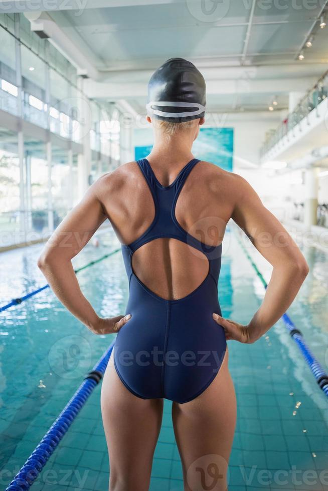 vista traseira do ajuste nadador por piscina no centro de lazer foto