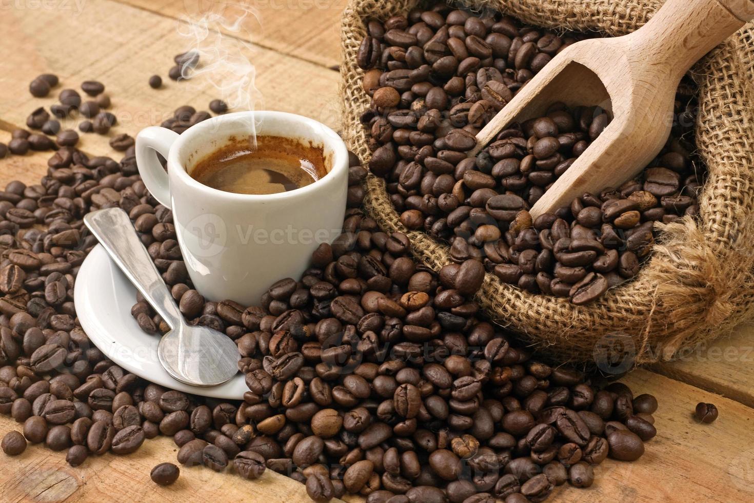 xícara de café e grãos na mesa de madeira foto