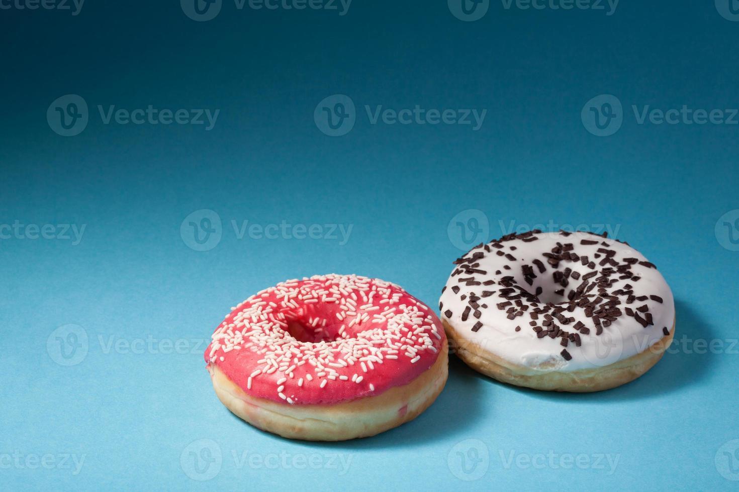 dois donuts com glacê vermelho e branco, isolado no azul foto