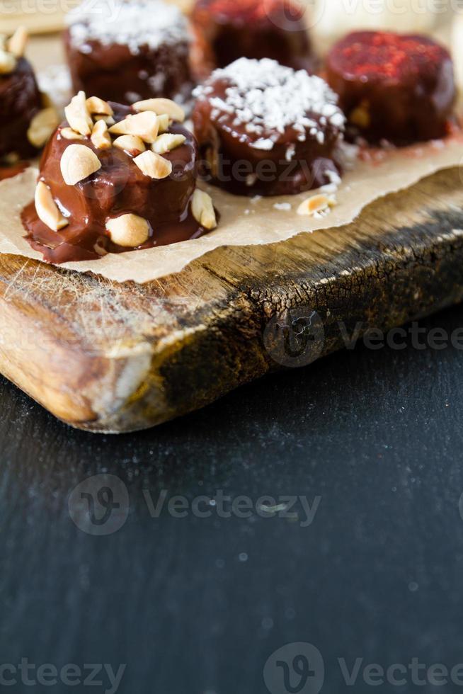 banana pops preparação - banana, chocolate, nozes, coco em pó foto