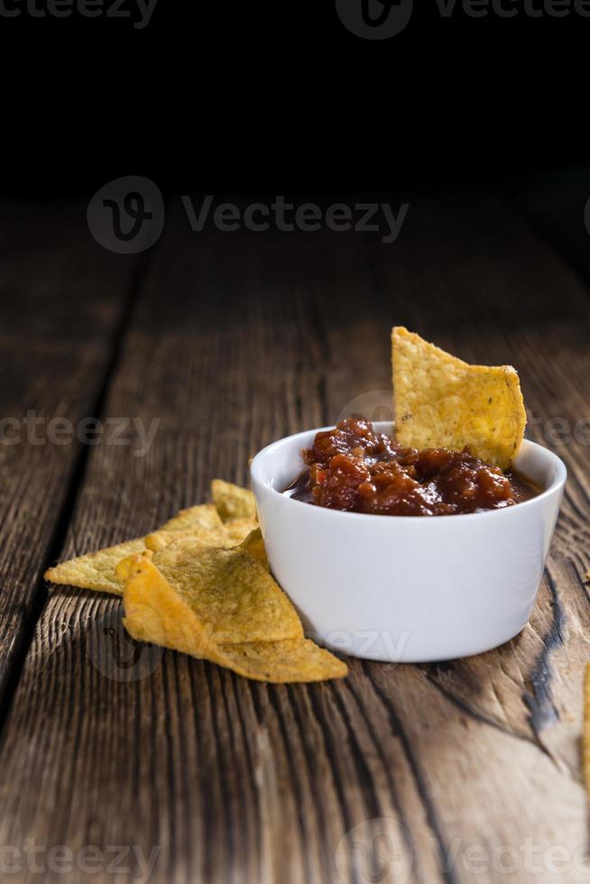 porção de nachos (com molho de salsa) foto