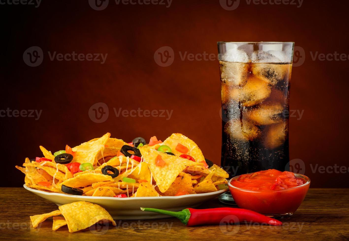 nachos, molho de salsa e bebida de cola foto