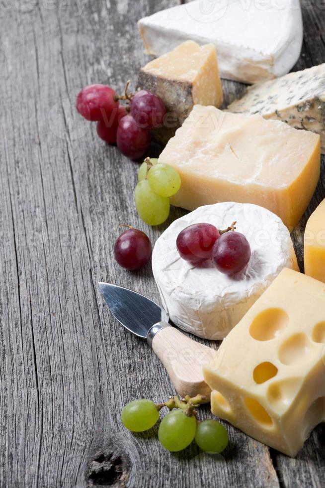 variedade de queijos e uvas em uma placa de madeira foto