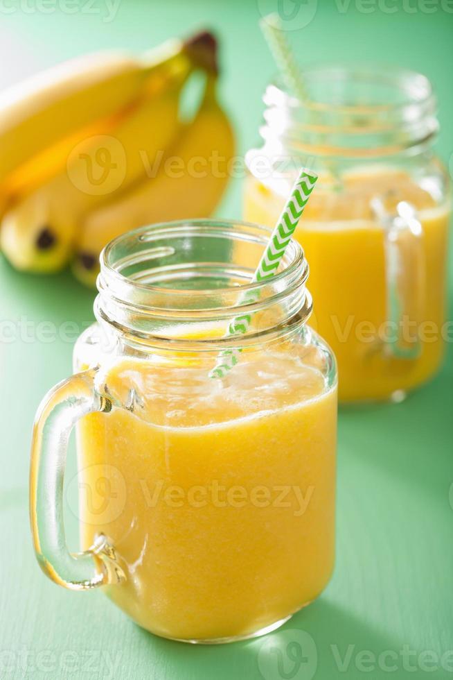 smoothie amarelo saudável com banana abacaxi manga em frasco de vidro foto