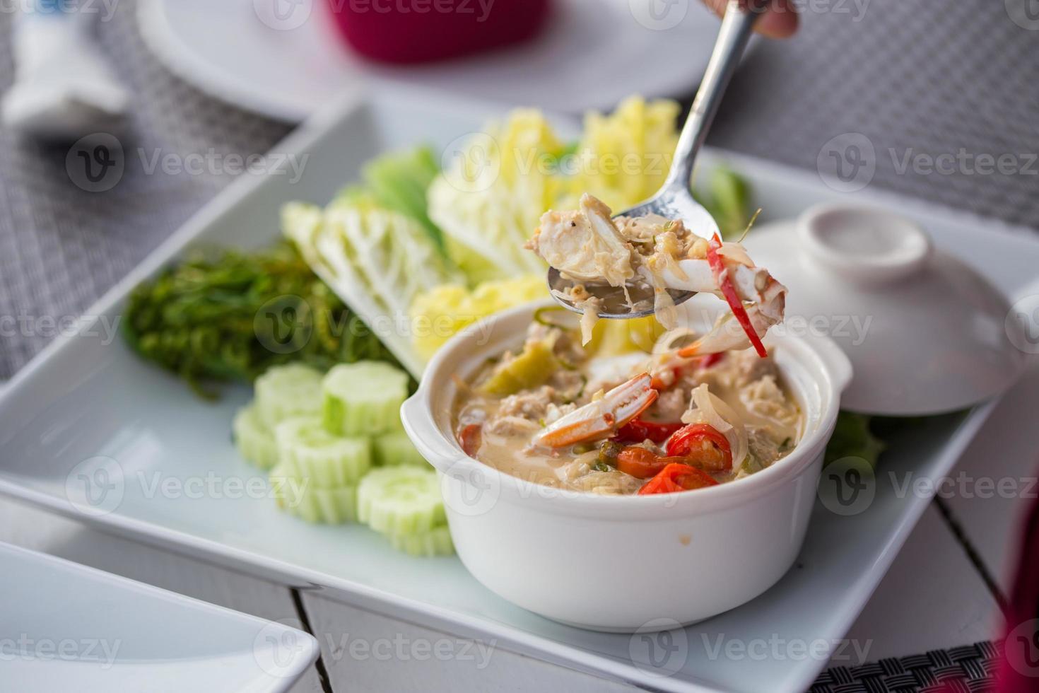 ensopado de caranguejo com molho de leite de coco com legumes frescos foto