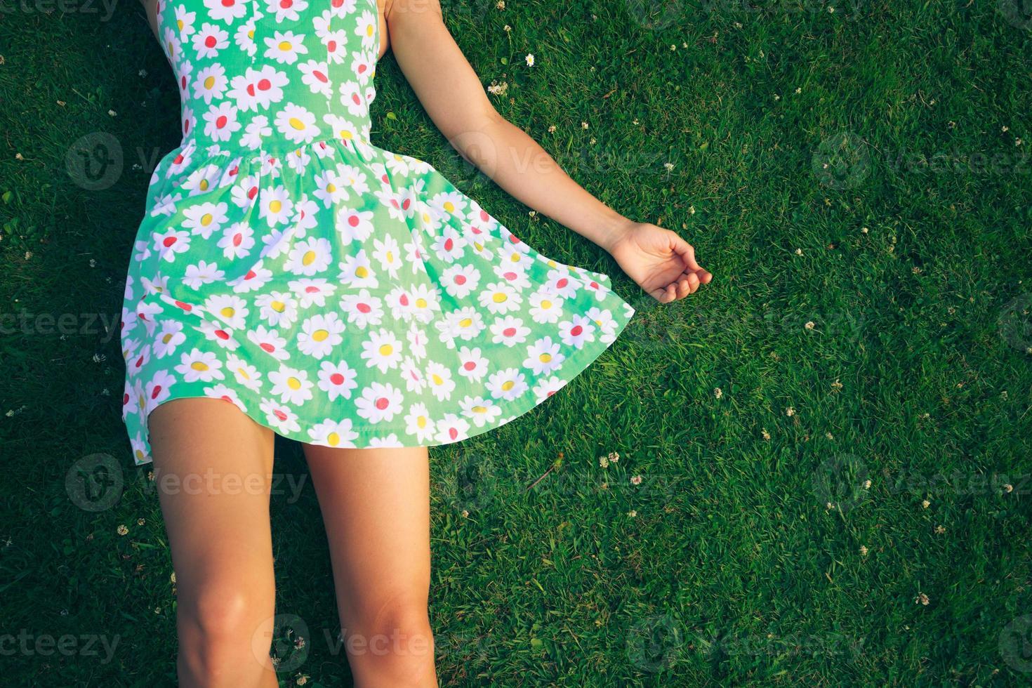 jovem mulher de vestido, deitado na grama foto