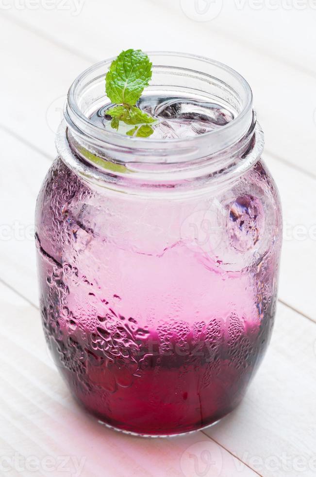 suco de uva vermelha refrigerado com refrigerante na placa de madeira branca foto