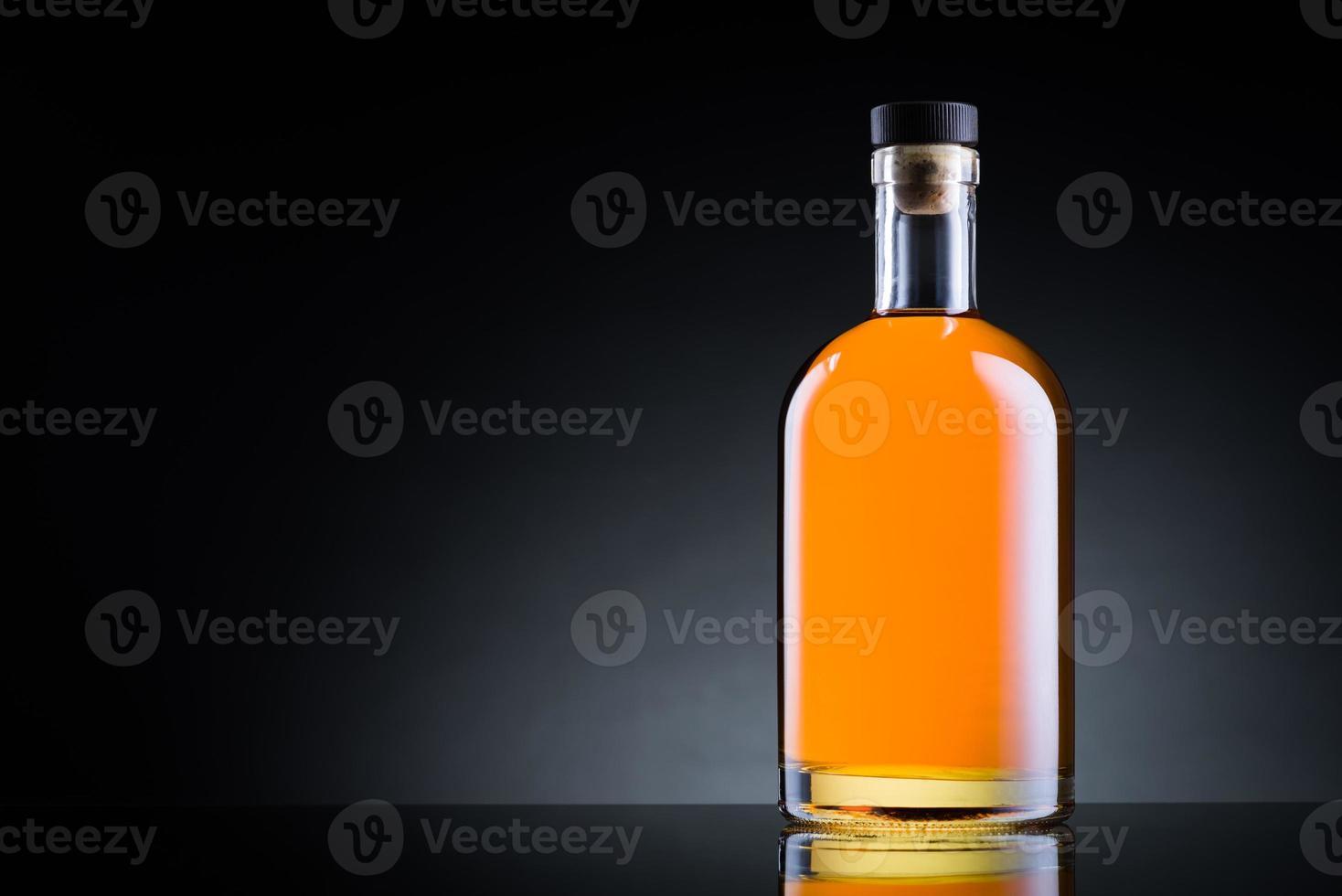 garrafa de uísque na superfície de vidro preto foto