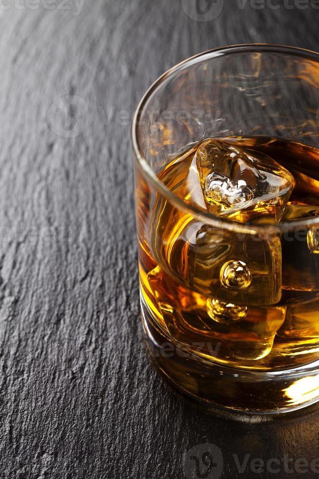copo de uísque com gelo na mesa de pedra preta foto