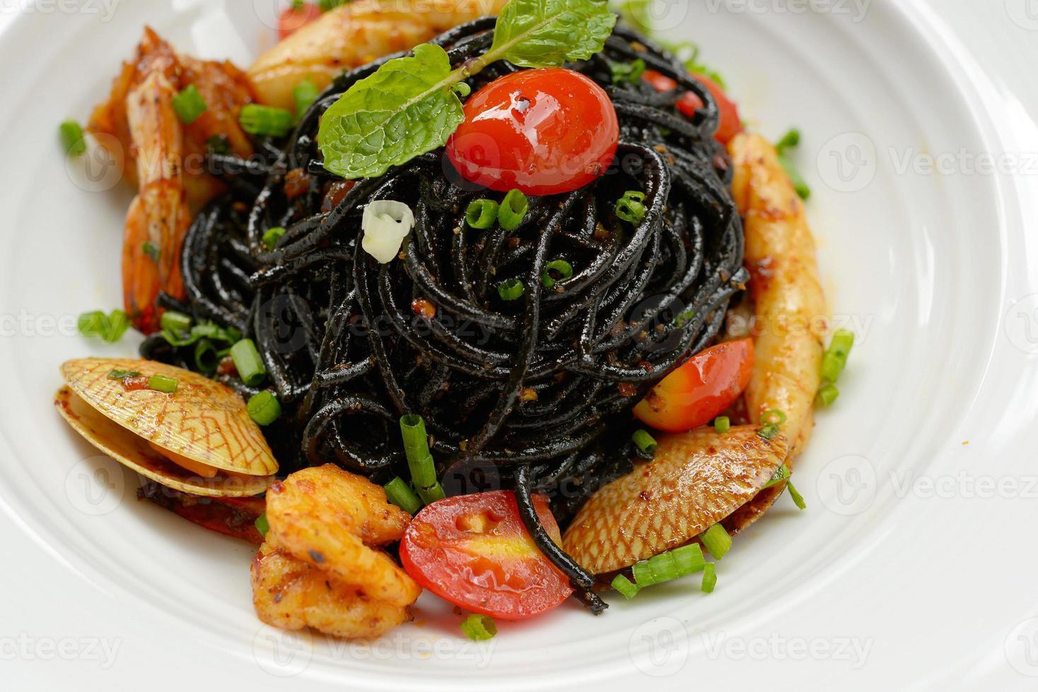 molho de espaguete preto, pimenta, frutos do mar. foto