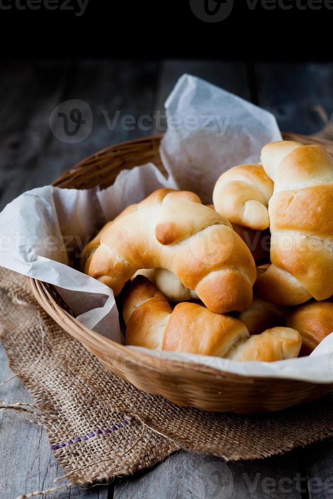rolos de manteiga pão na cesta de vime contra fundo rústico escuro foto