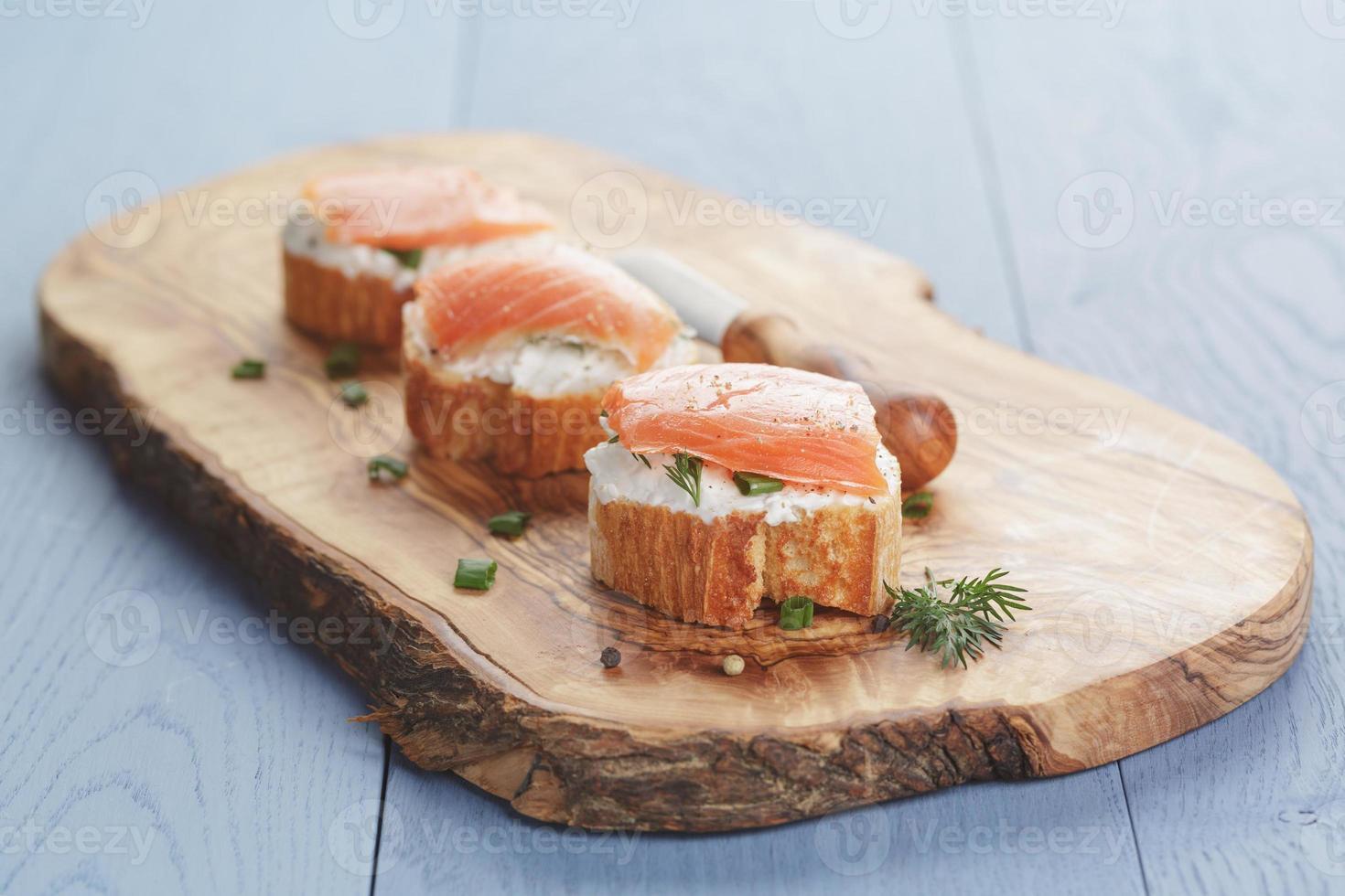 pequenos sanduíches com queijo e salmão na mesa de madeira foto