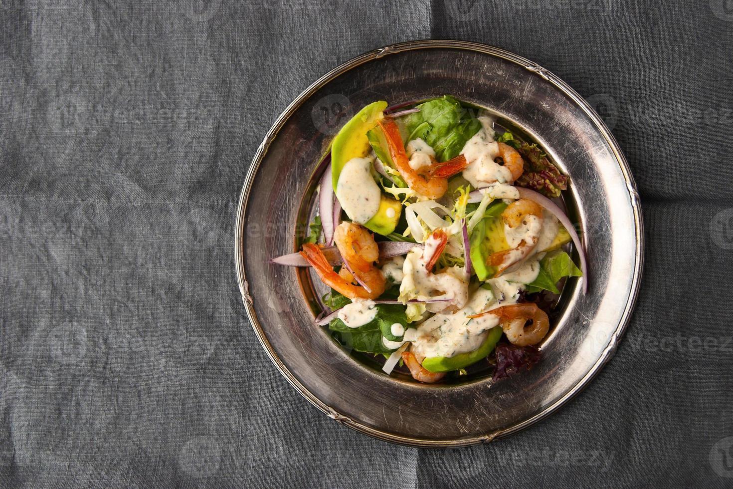 salada de camarão e abacate na placa de metal vintage na toalha de mesa cinza foto