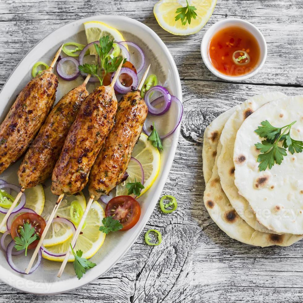 espetadas de frango em um prato oval e tortilla caseira foto