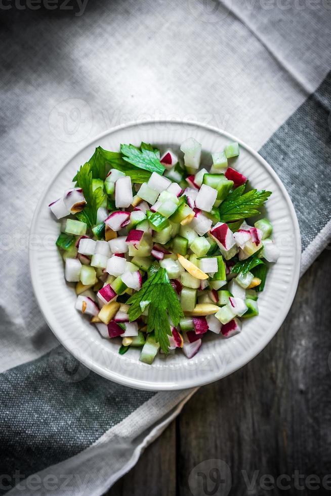 salada de legumes em fundo de madeira foto