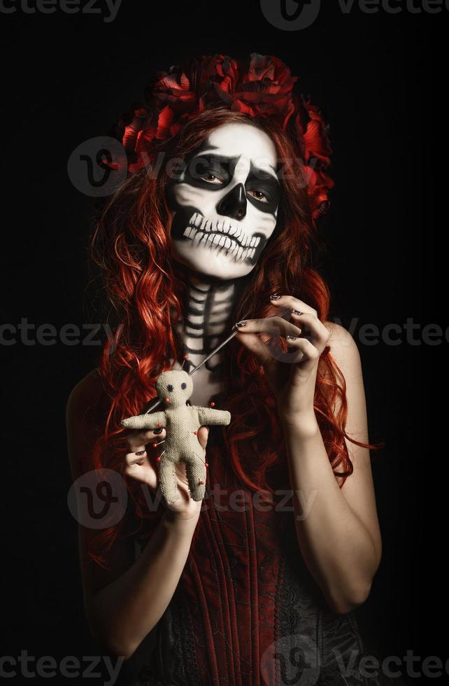 jovem mulher com maquiagem calavera (caveira de açúcar) piercing boneca de vodu foto