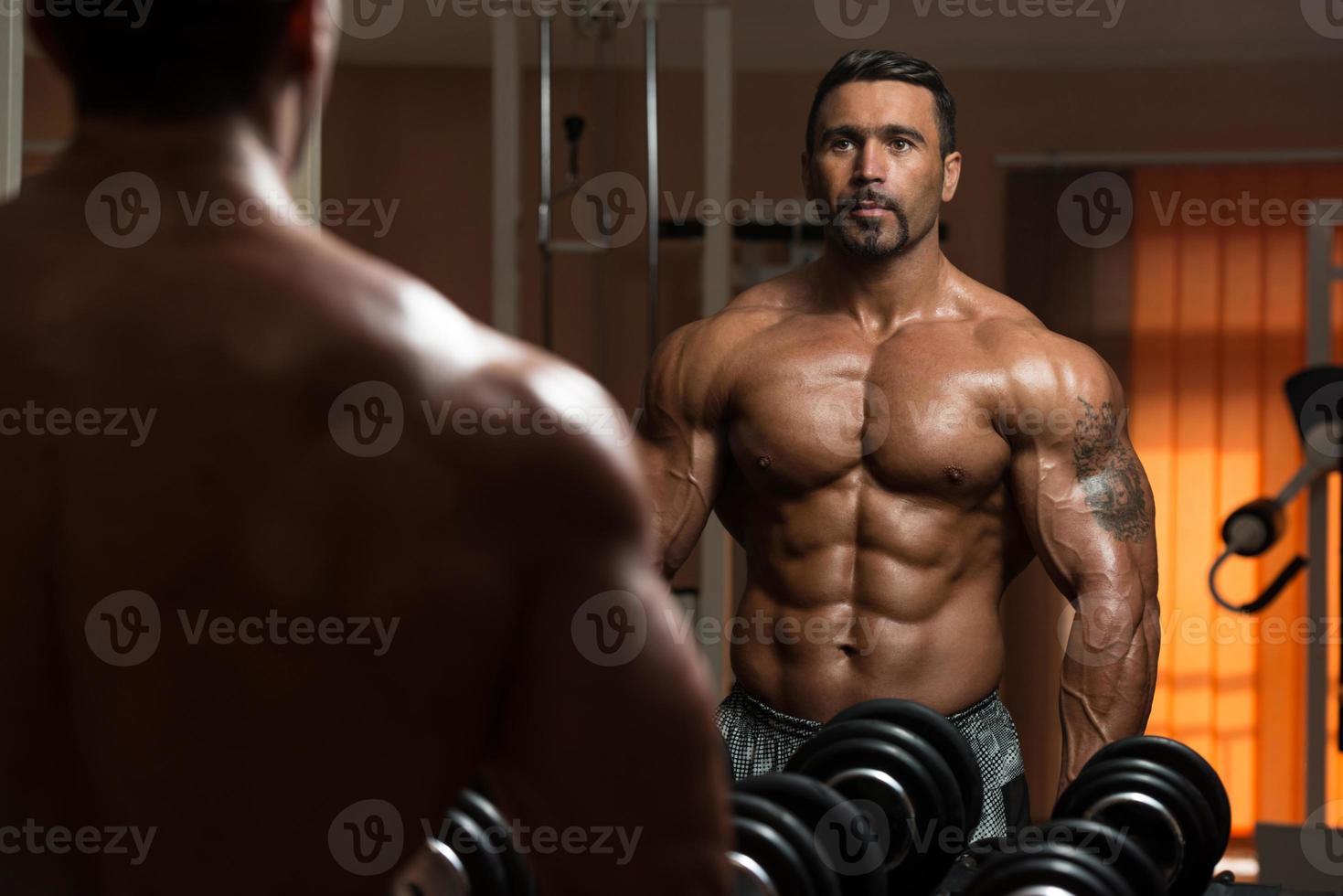 fisiculturista exercitar bíceps, olhando para o próprio reflexo foto