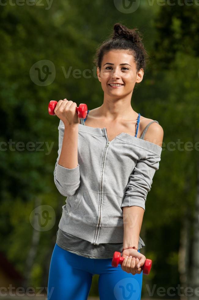 mulher sorrindo e levantando pesos foto