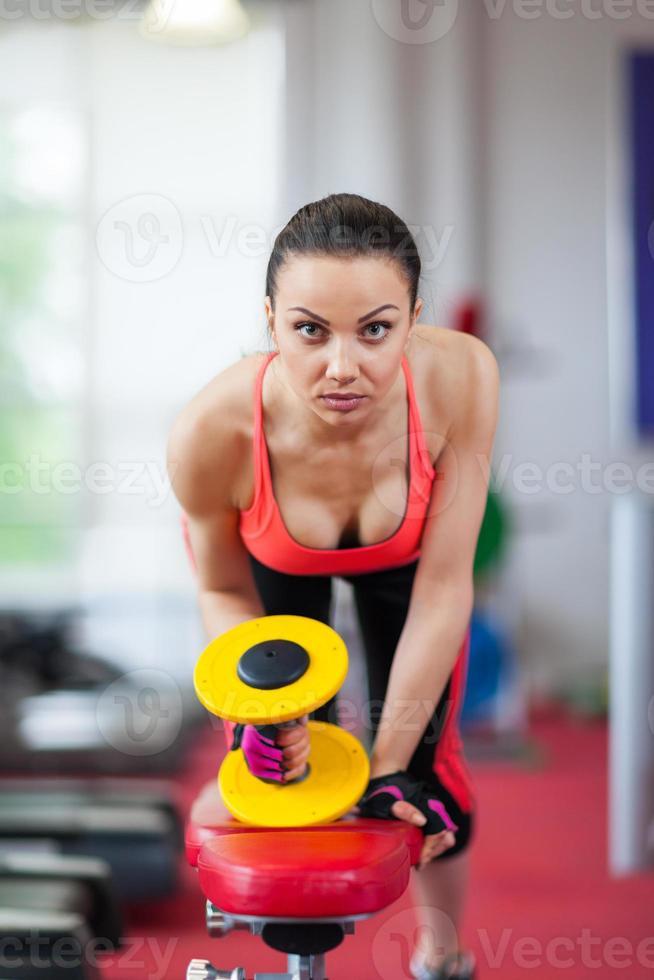mulher no esporte ginásio exercitar com halteres foto