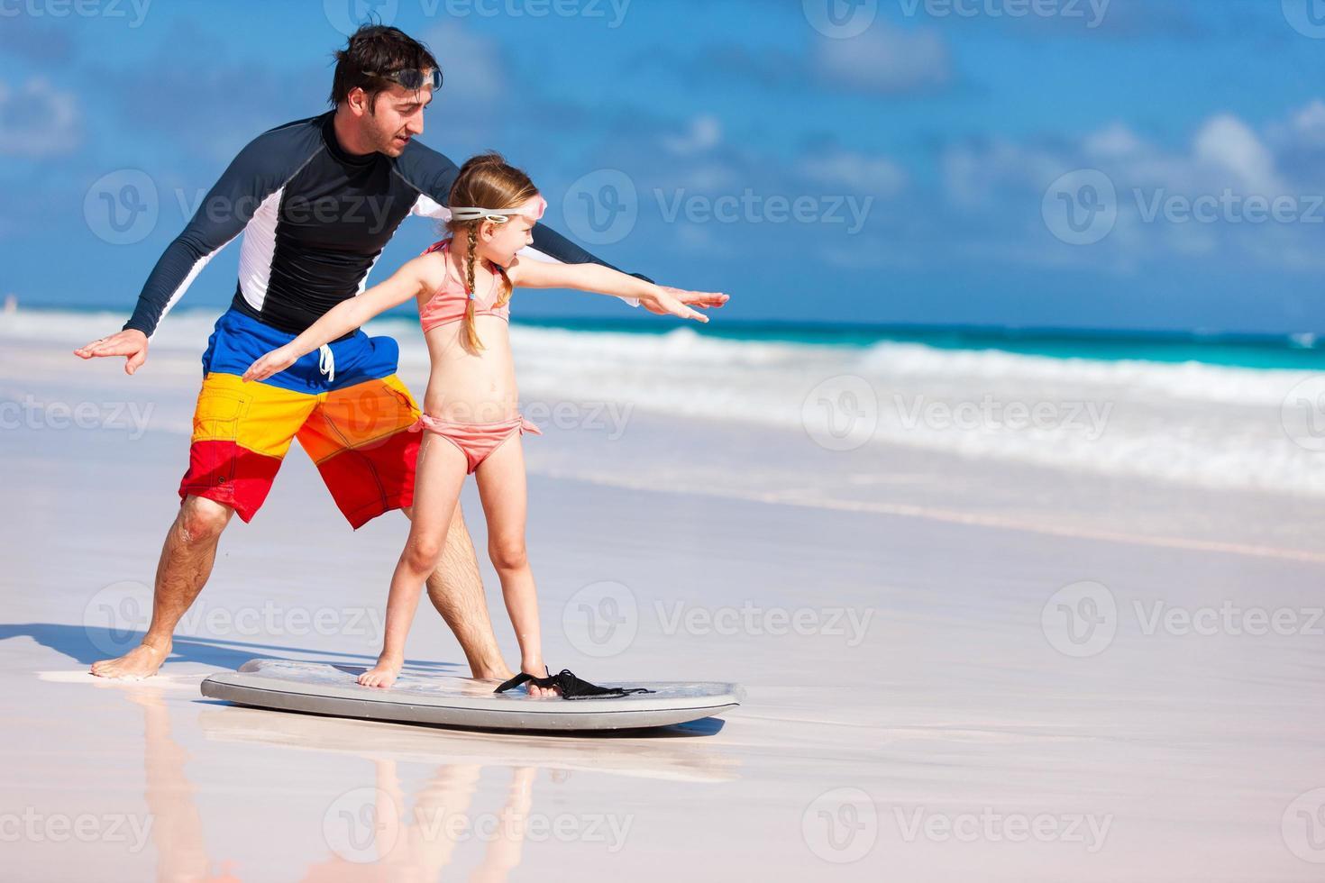 pai e filha praticando surf foto