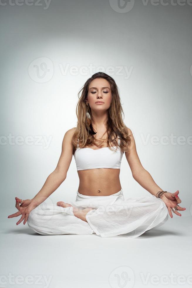 pose de ioga jovem no estúdio em fundo branco foto