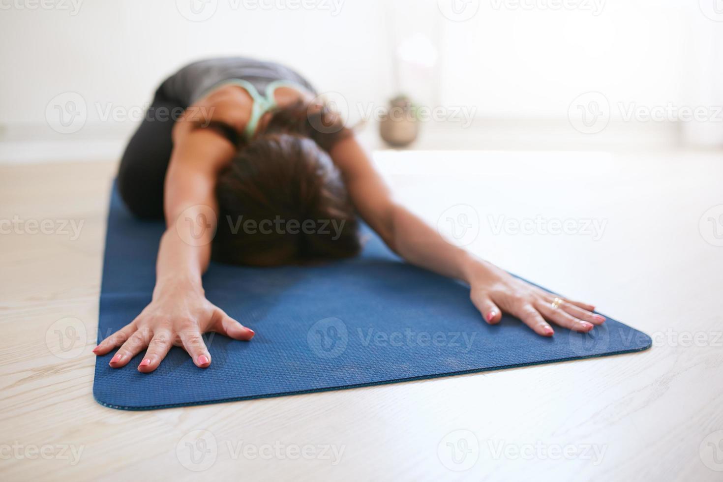 mulher relaxante em pose de criança fazendo yoga foto