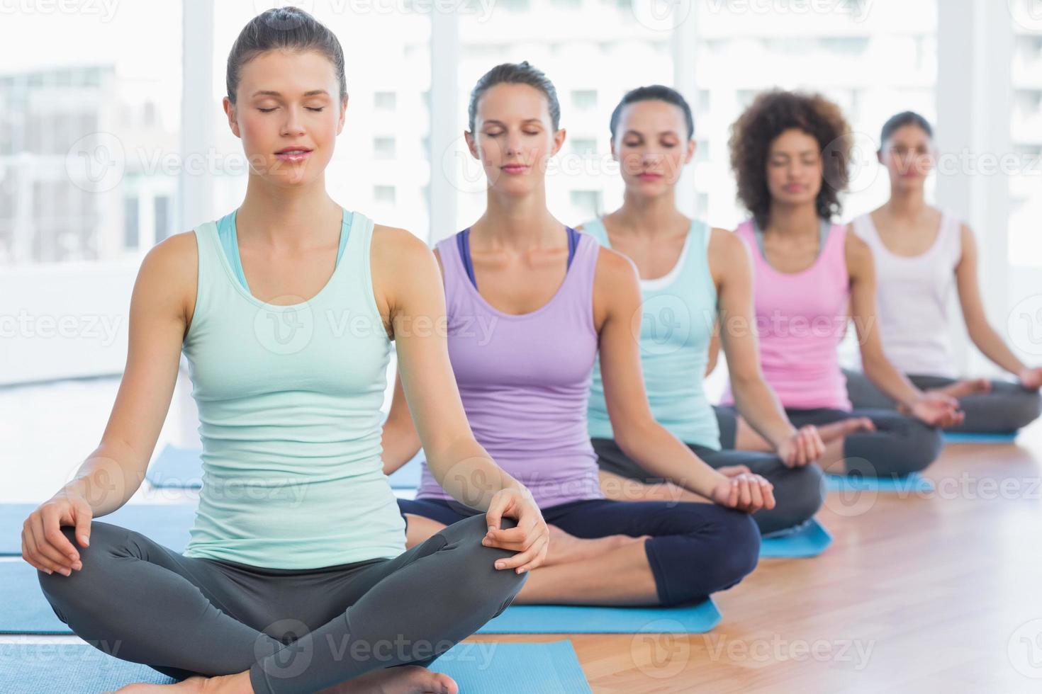 mulheres desportivas em pose de meditação com os olhos fechados foto