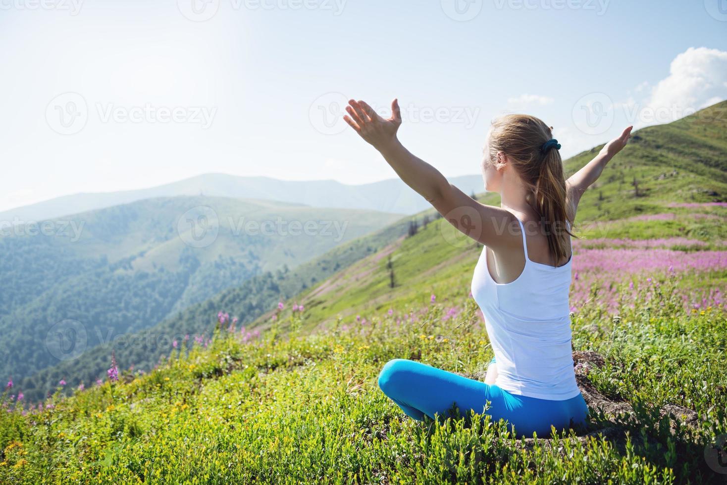 jovem mulher meditar no topo da montanha foto