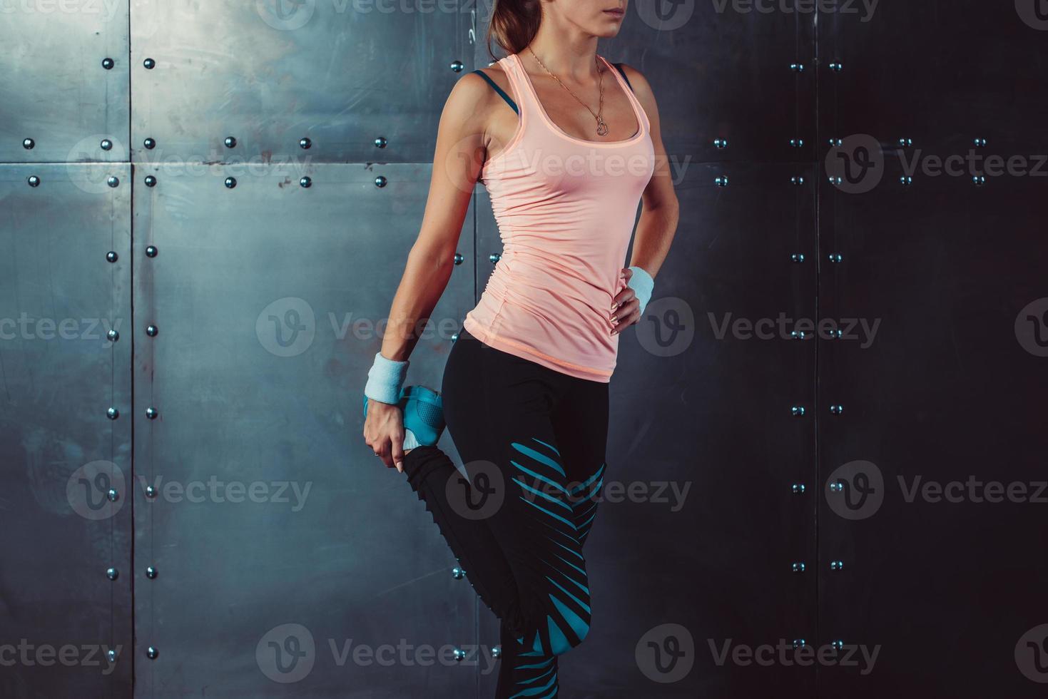 mulher de fitness, esticando as pernas ajuste corredor feminino fazendo alongamentos foto