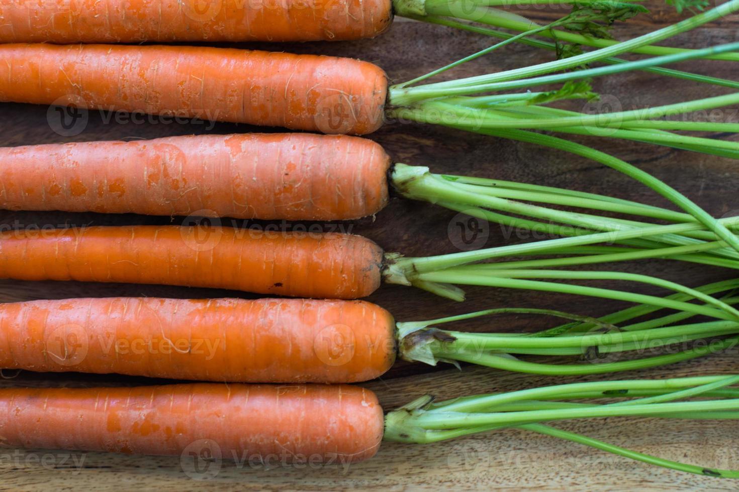 linha de cenouras na tábua de madeira foto