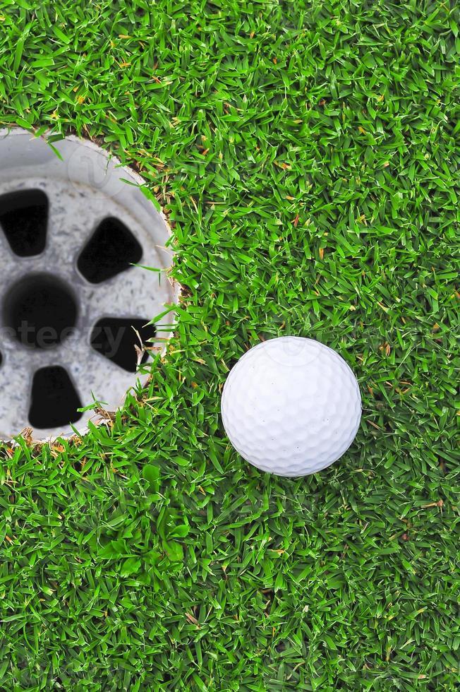 bola de golfe no lábio da taça foto