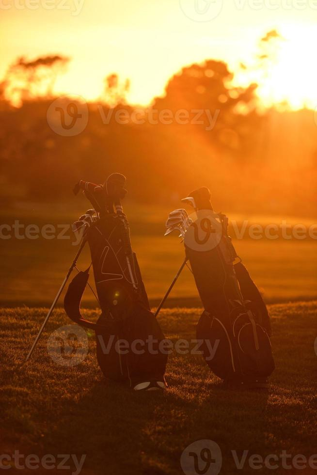 sacos de golfe ao pôr do sol foto