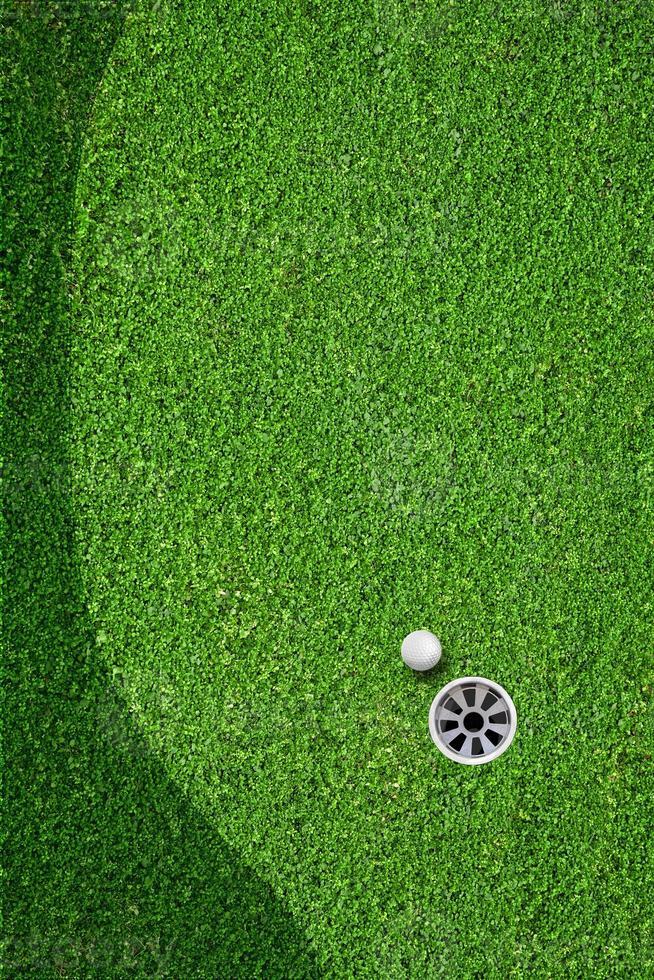 a bola no buraco no campo de golfe foto