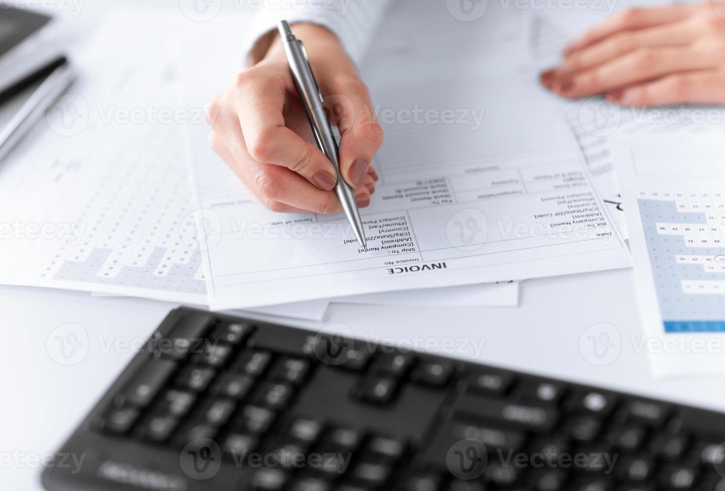close-up de mãos de mulher preenchendo papel fiscal foto