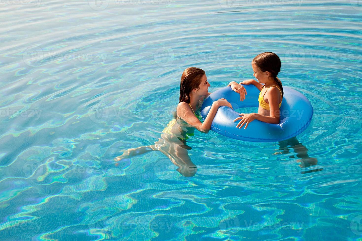 meninas com anel inflável na piscina foto