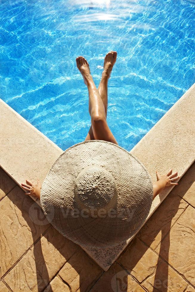 mulher sentada à beira da piscina foto