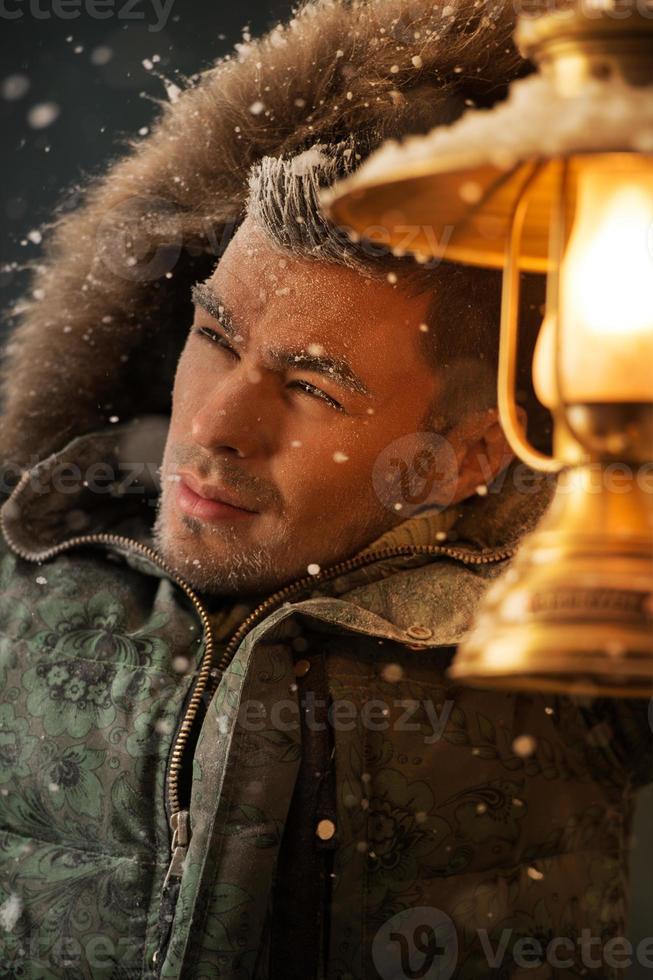 homem brutal andando sob tempestade de neve durante a noite iluminando seu caminho foto