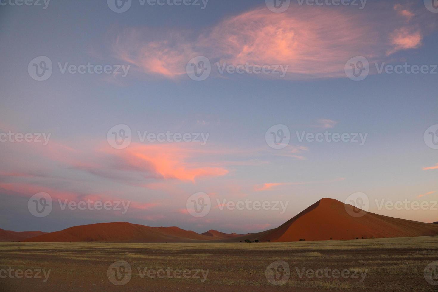nuvens rosa inchadas sobre dunas de areia vermelhas foto