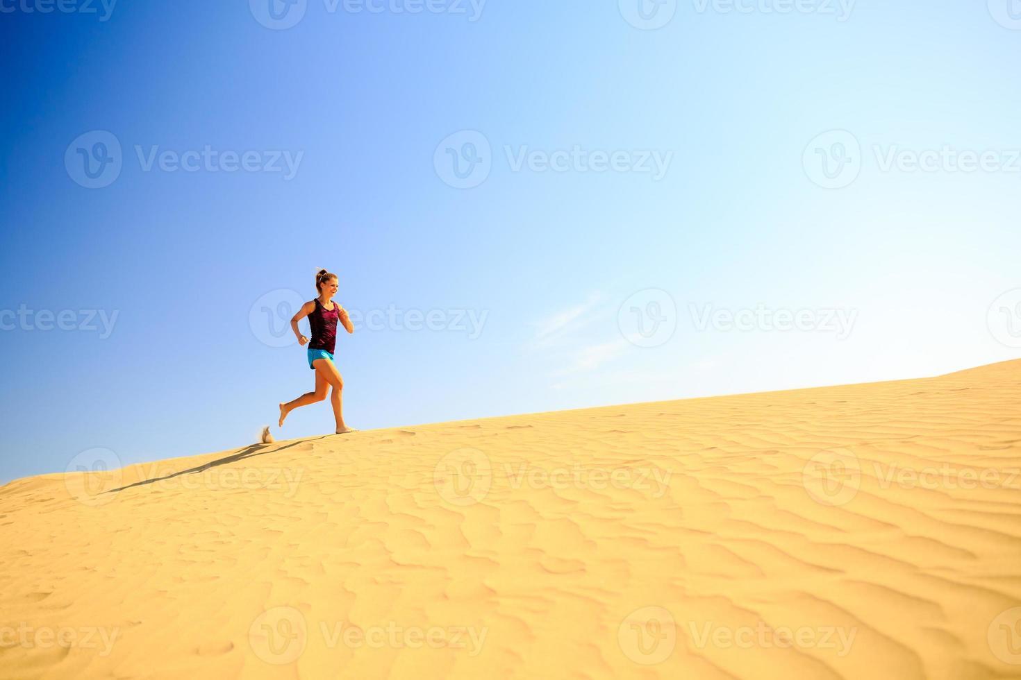 mulher feliz correndo correndo nas dunas de areia foto