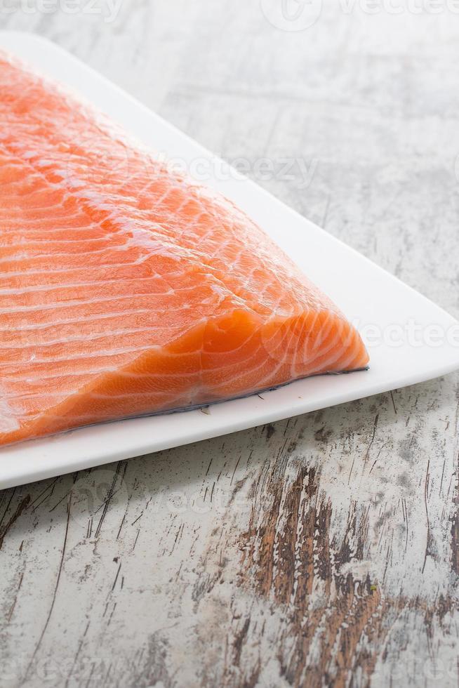 deliciosa porção de filé de salmão fresco sobre fundo vintage de madeira foto