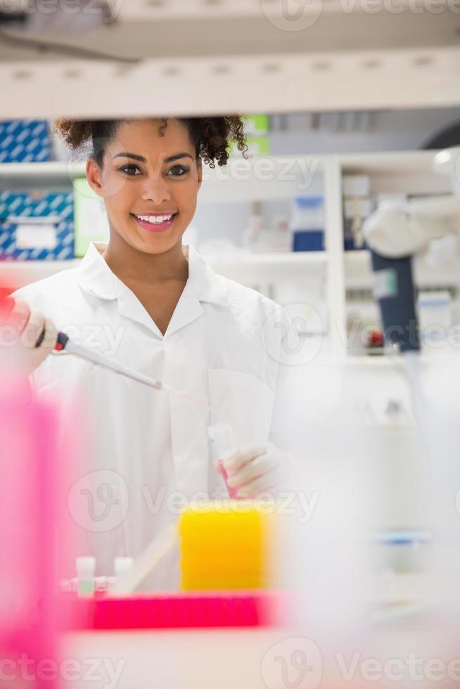 estudante de ciência bonita sorrindo e segurando o copo foto
