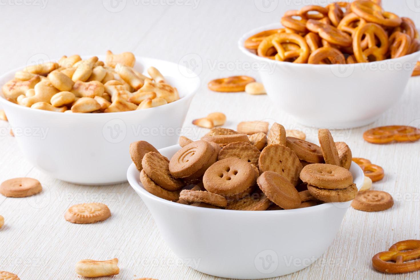 biscoitos salgados e doces em pequenas tigelas foto