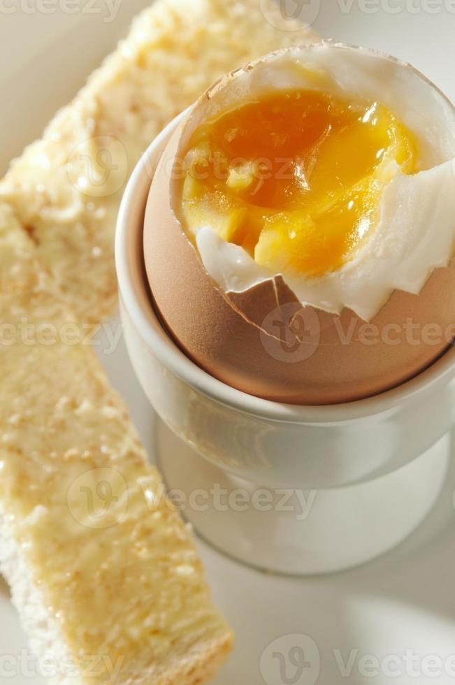 ovo cozido no ovo em cima com soldados torradas com manteiga foto