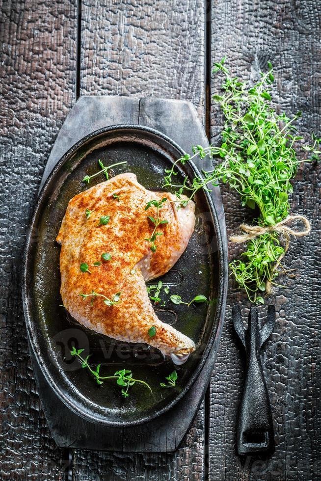 pedaço de frango com manjerona fresca foto